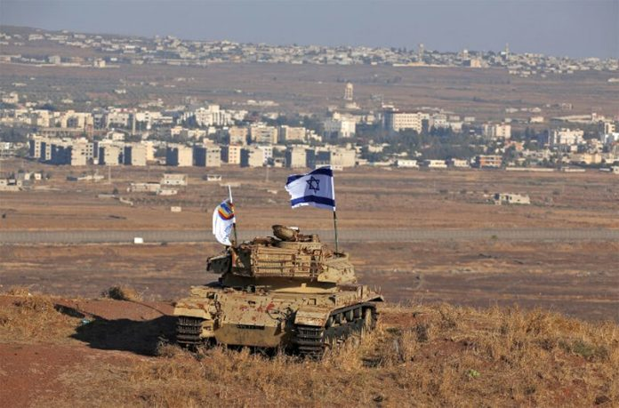 An Israeli flag flutters above the wreckage of an Israeli tank sitting on a hill in the Israeli-occupied sector of the Golan Heights (Photo by Jalaa Marey / AFP)