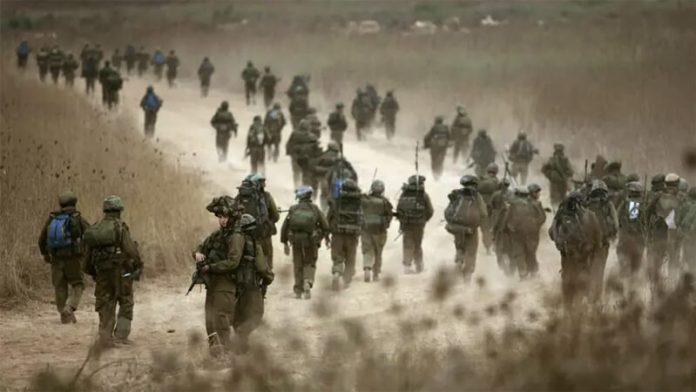 Israeli paratroopers walk a dirt road on their way to a Lebanese village during the Second Lebanon War, Aug. 12, 2006