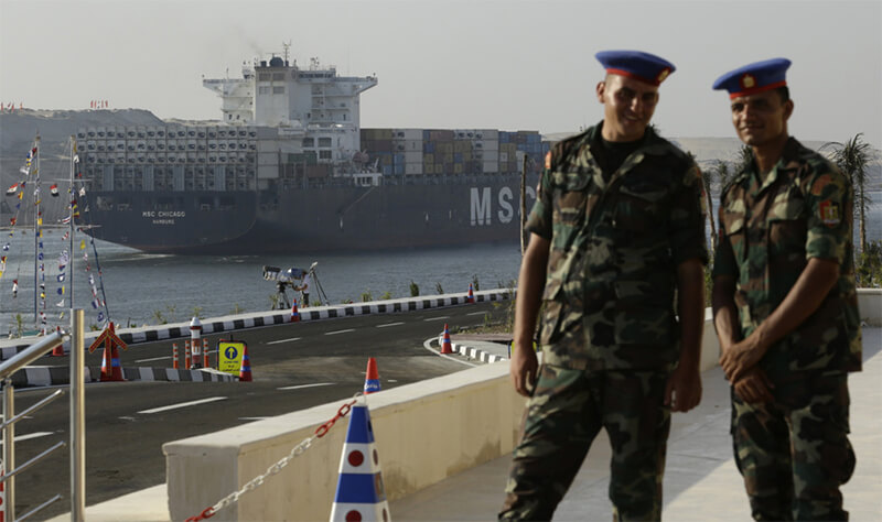 Soldiers watch a cargo container ship cross the new section of the Suez Canal after the opening ceremony in Ismailia, Egypt, 6 August 2015. (photo AP Hollandse Hoogte ⁃ Hassan Ammar)